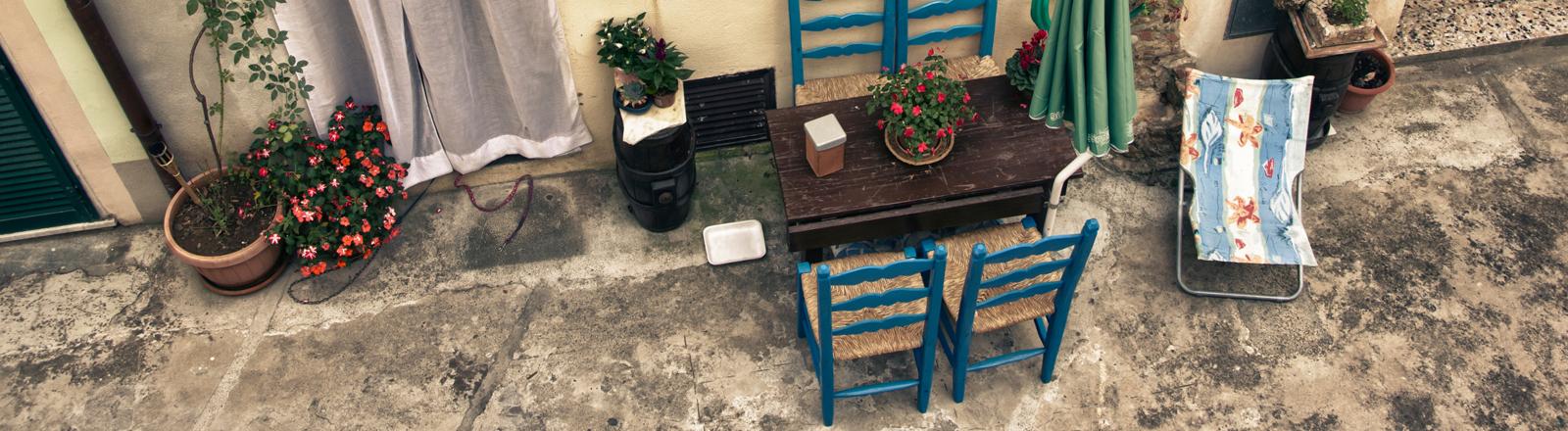 Tisch mit Stühlen vor einem Haus mit südlichem Flair.