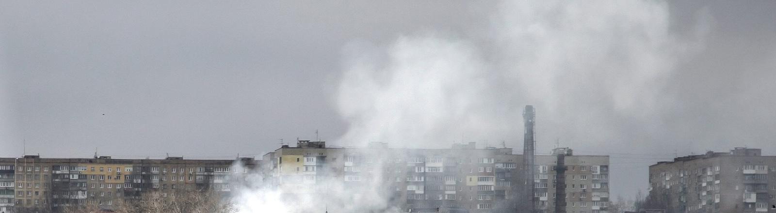 Häuser von Donezk, über denen Rauch aufsteigt.