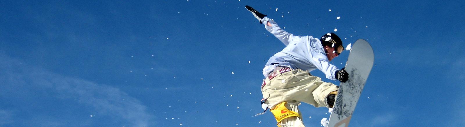 Person auf einem Snowboard vor blauem Himmel