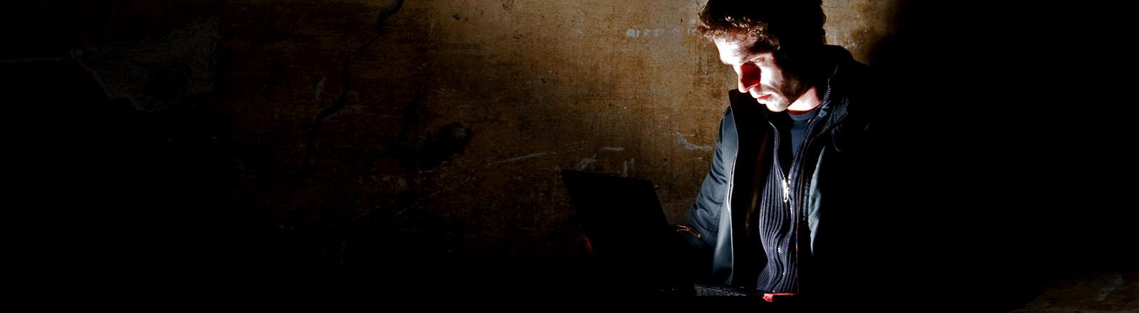 Ein Mann betrachtet im Dunkeln den Bildschirm seines Notebooks