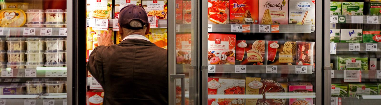 Ein Mann nimmt in einem Supermarkt ein Produkt aus einem Tiefkühlschrank.