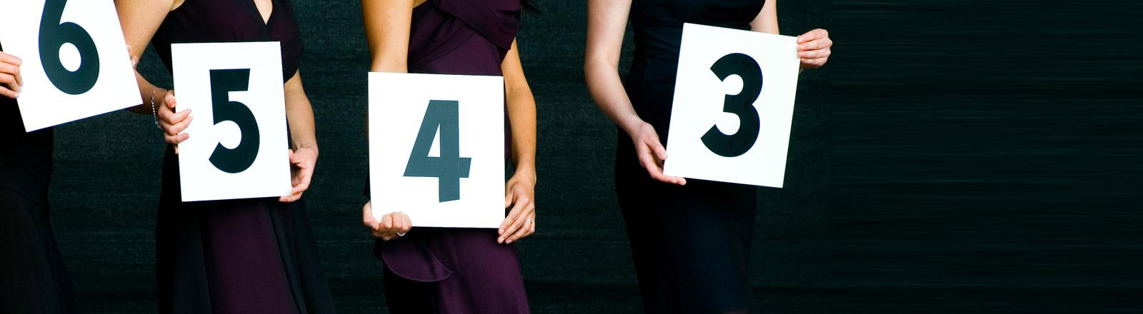 Nummerngirls halten Schilder mit Nummern hoch.