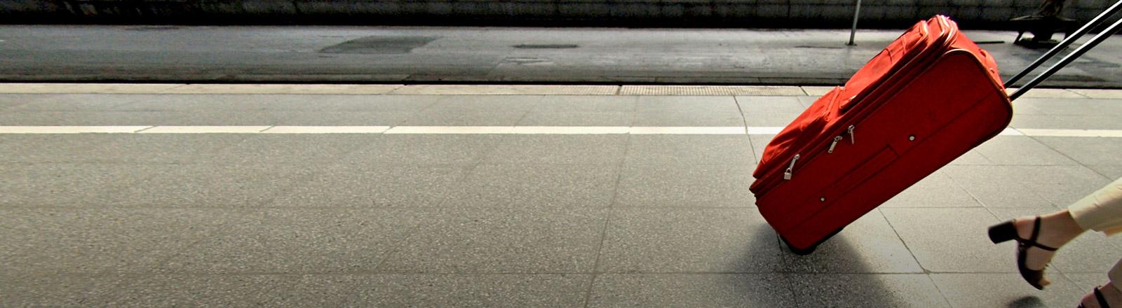 Eine Frau zieht einen Trolley über einen Bahnsteig.