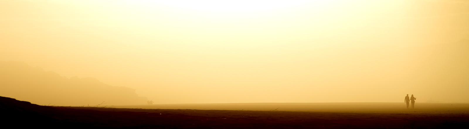 Zwei Menschen gehen in der prallen Sonne spazieren.