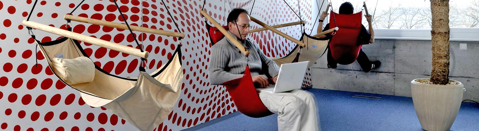 Google-Büro. Ein Mann sitzt mit Laptop in einer Hängematte.