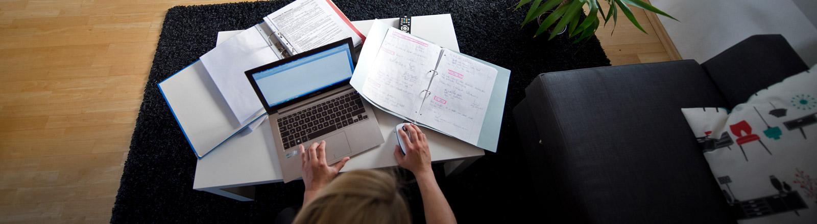 Eine Frau arbeitet zu Hause am Wohnzimmertisch an ihrem Computer.