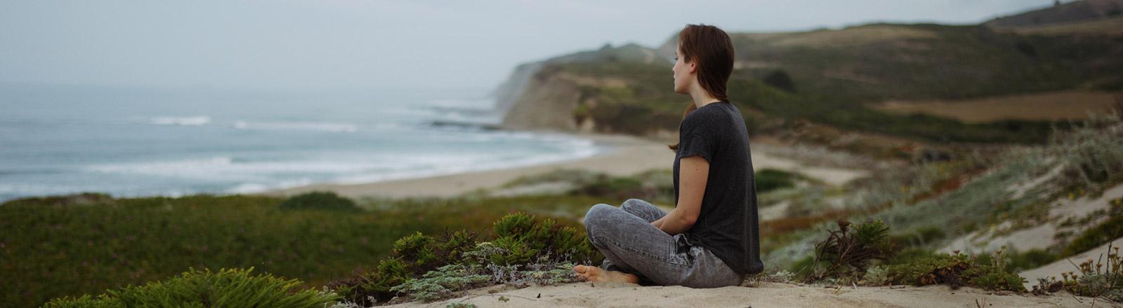 Laura Zalenga sitzt auf einem Felsen an einem Strand.