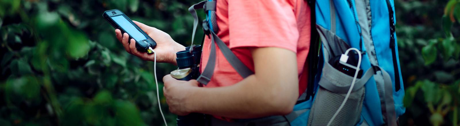 Ein Mann mit Rucksack hält ein Smartphone in der Hand.