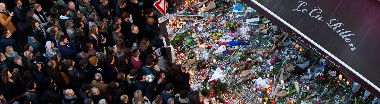 Viele Menschen trauern vor dem Restaurant Carillon in Paris.
