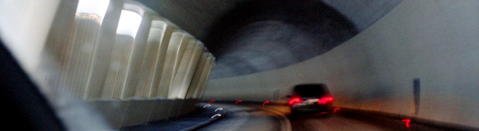 Verschwommene Autorücklichter in einem Tunnel.