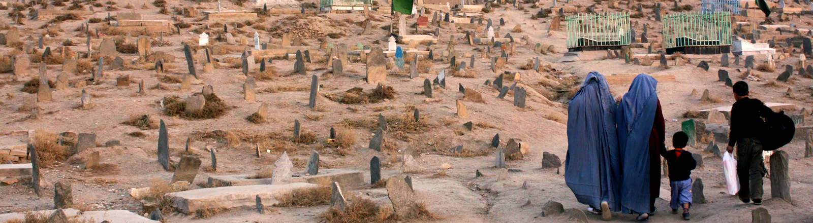 Ein Friedhof in der Nähe von Kabul. Frauen und Kinder gehen den Friedhof entlang 2010.