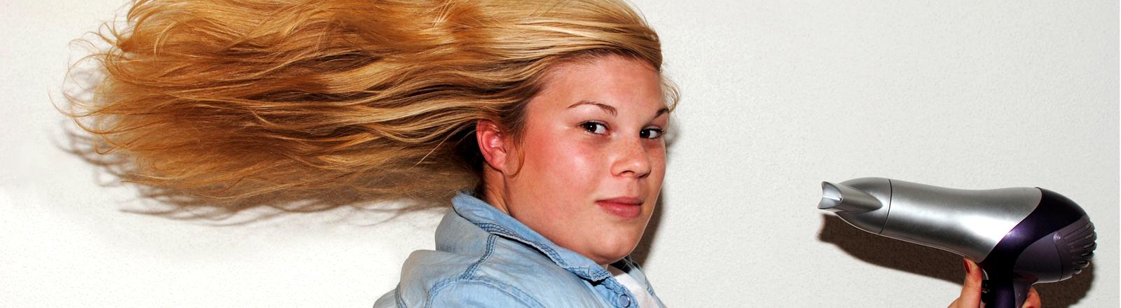 Eine Frau mit einem Fön in der Hand und wehenden Haaren.