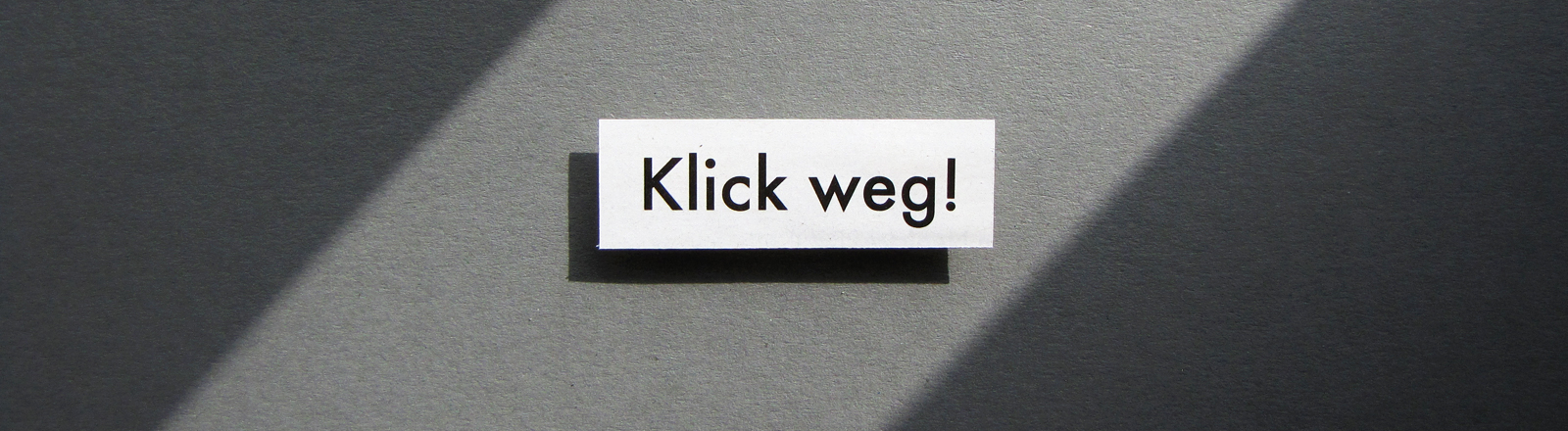 """Ein Schild mit der Aufschrift """"Klick weg"""" vor grauem Hintergrund."""