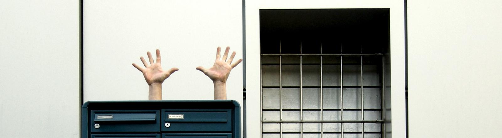 Hande hoch hinter einem Briefkasten vor einer Hauswand
