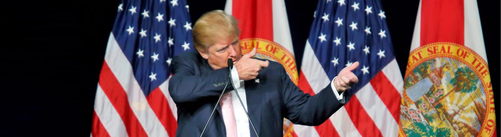 Donald Trump macht eine Schießbewegung auf einem Podium vor USA-Flaggen.