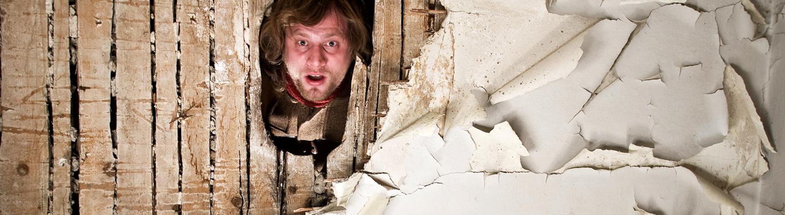 Ein Mann guckt durch eine zerstörte Wand.
