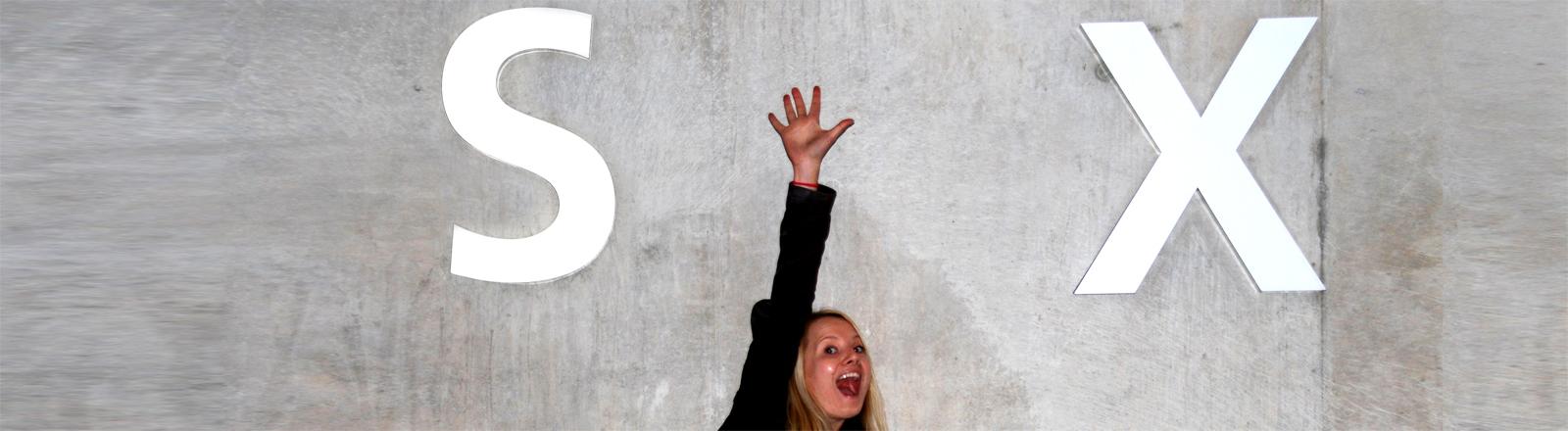 Eine junge Frau hebt die Hand vor den Buchstaben S und X.