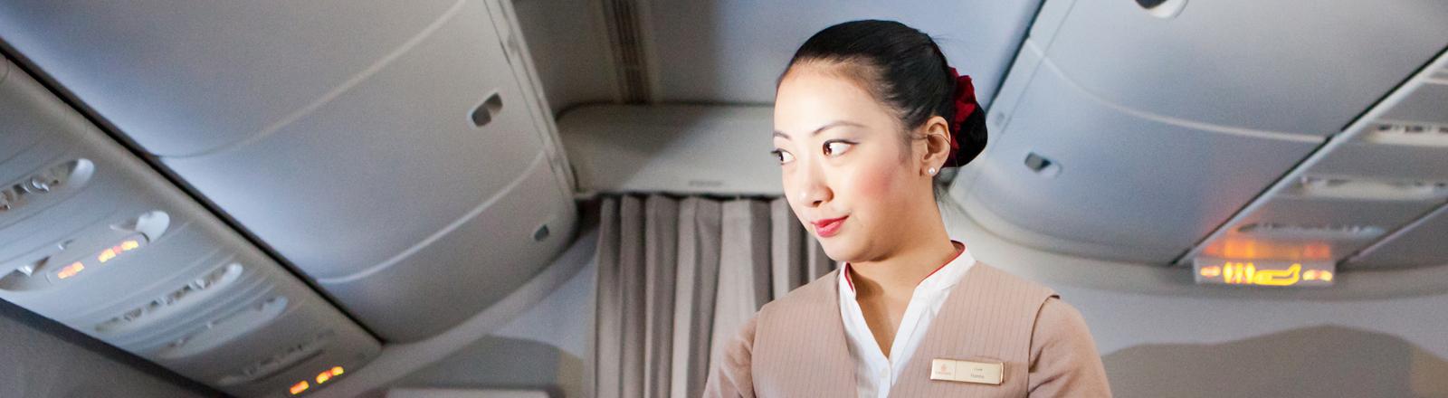 Stewardess serviert Orangensaft und Wasser