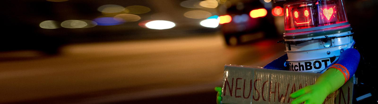 """Der Roboter Hitchbot hält ein Schild hoch mit der Aufschrift """"Neuschwanstein"""""""
