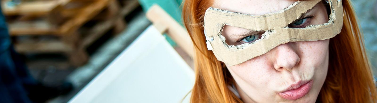 Eine junge Frau mit einer Maske zieht eine Grimasse.