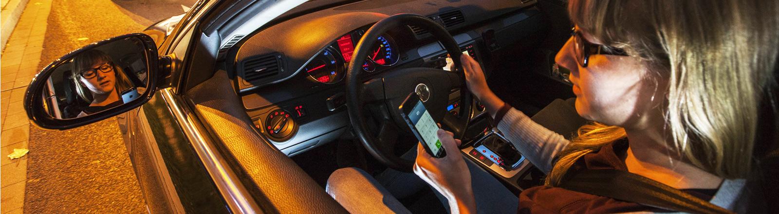 Eine Frau schaut im Auto auf ihr Handy