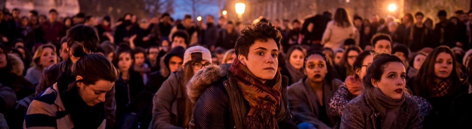 Junge Leute sitzen während einer Demo in der Nacht am Platz der Republik in Paris.