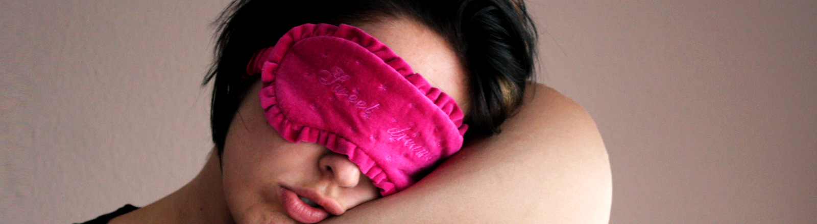 Verschlafene Frau mit Augenmaske
