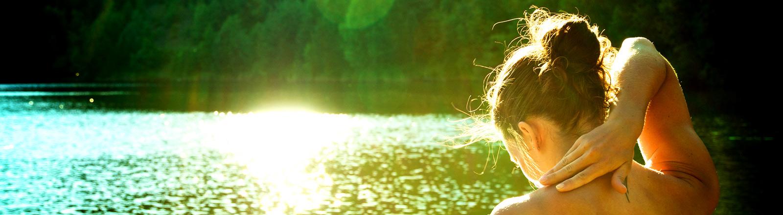 Eine junge Frau steht im Sonnenschein in einem See.