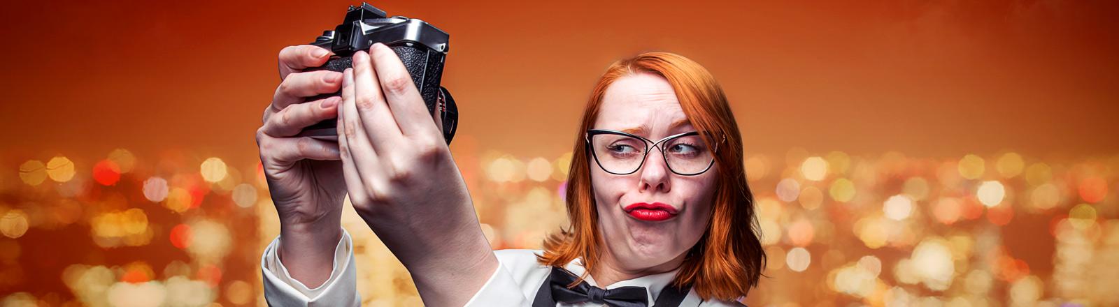 Eine Frau im weißen Smoking zieht eine Fotogrimasse.