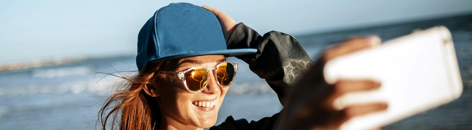 Frau mit Sonnenbrille und iphone am Strand
