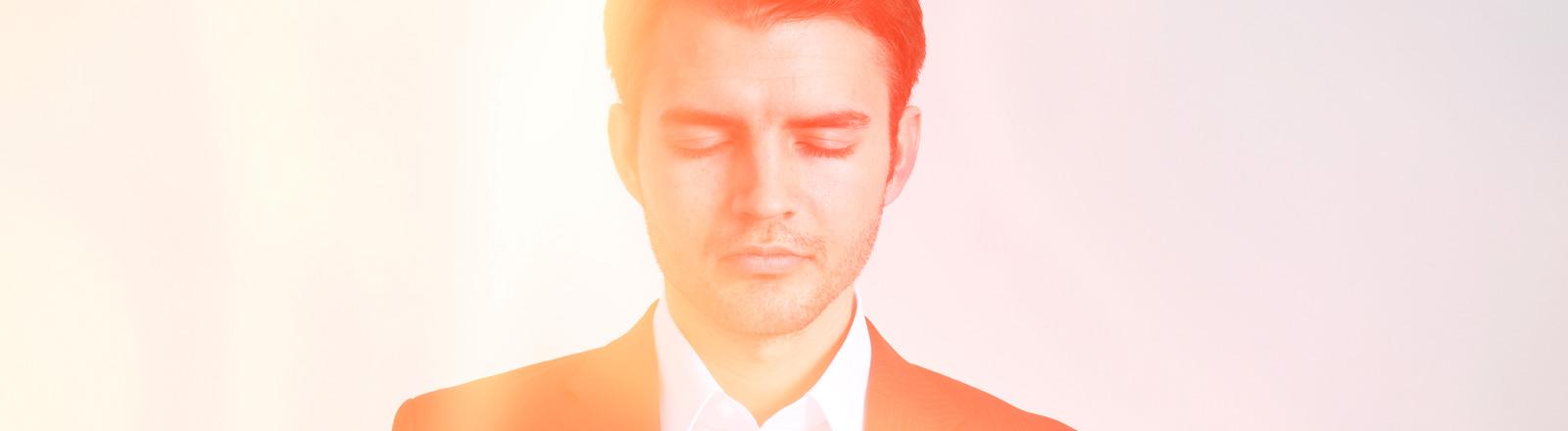 Ein Mann im Anzug schaut verträumt.