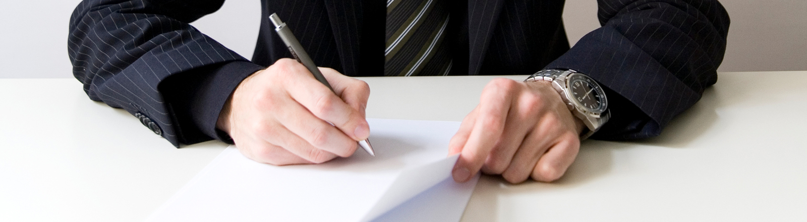 Mann im Anzug, der etwas auf ein Blatt schreibt.