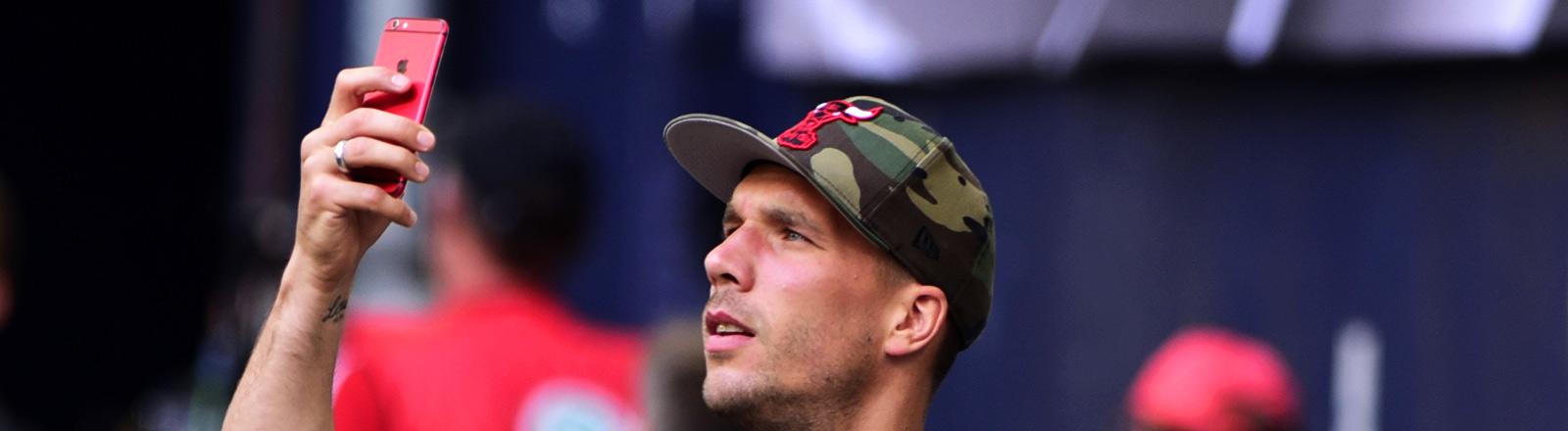 Lukas Podolski fotografiert im Stadion mit seinem Handy