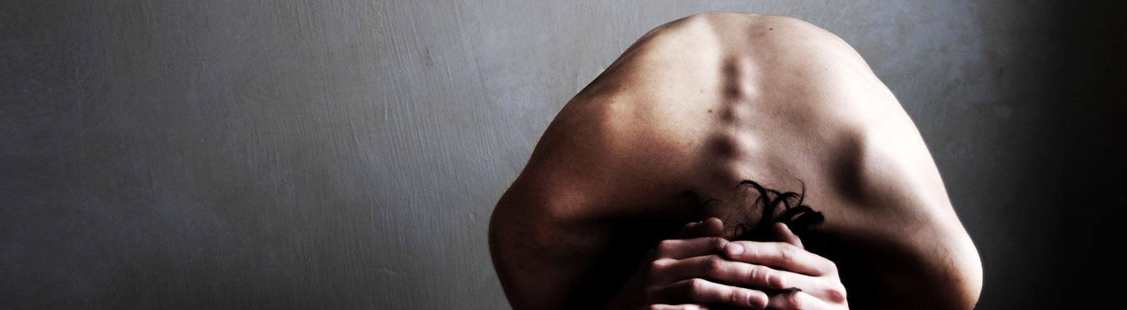Ein Mann verrenkt seinen nackten Oberkörper, so dass die Wirbelsäule hervorsticht