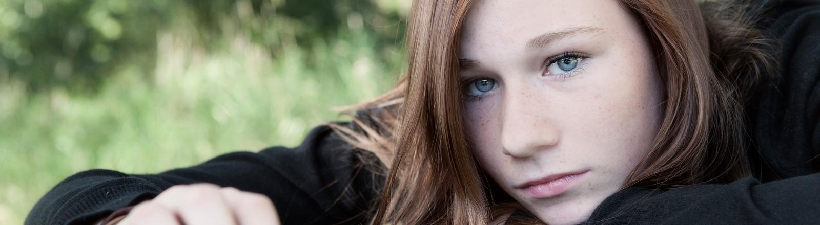 Eine junge Frau schaut gelangweilt