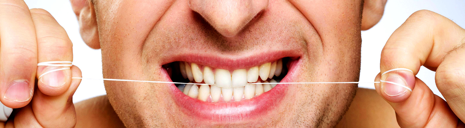 Ein Mann benutzt Zahnseide