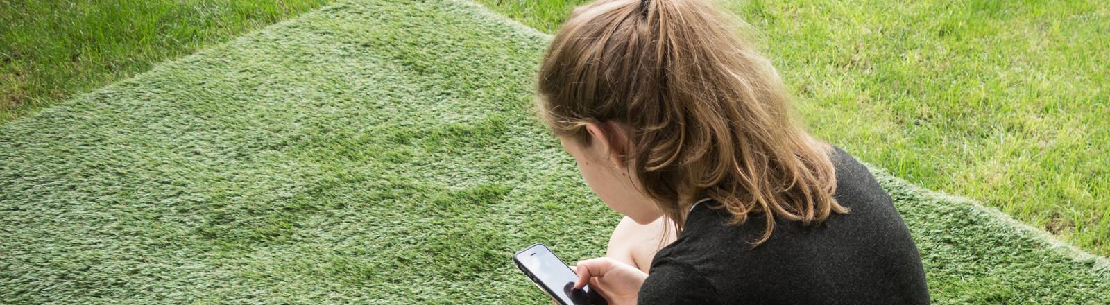 Frau mit Smartphone auf Rasen sitzend