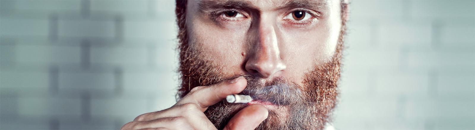 Man raucht mit ernstem Blick