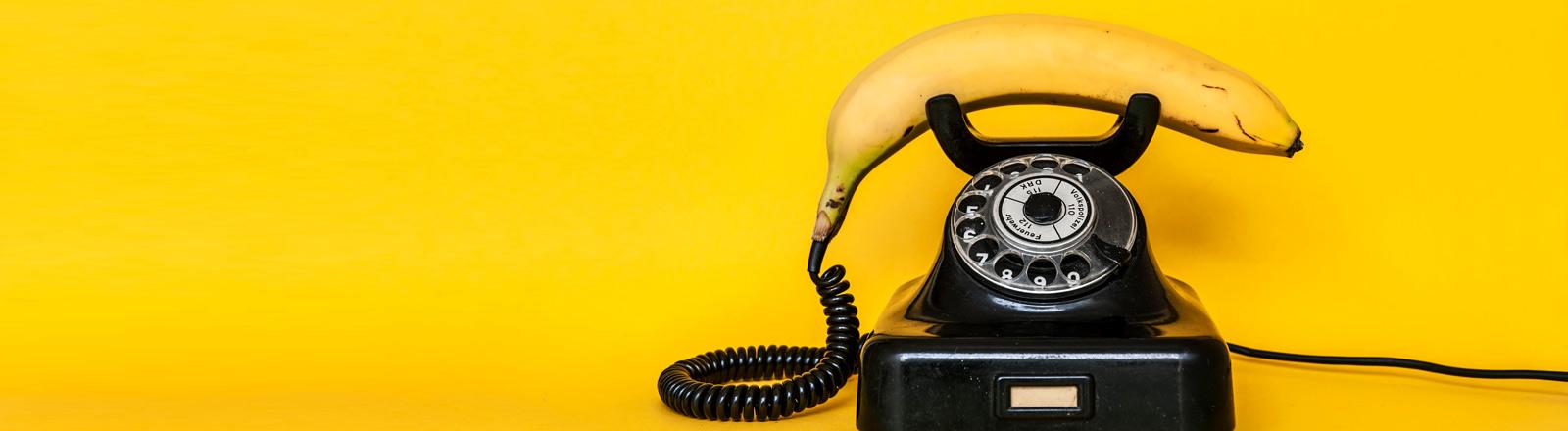 Eine Gorillahand greift zum Bananen-Telefonhörer