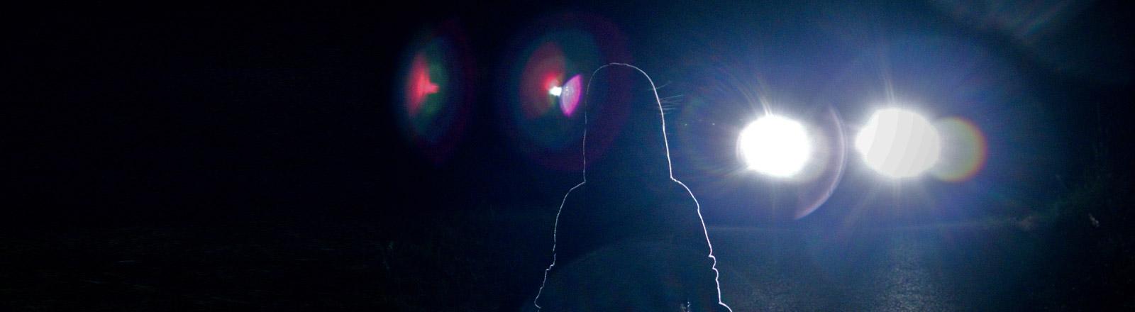 Ein Kind steht nachts auf einer Straße, ein Auto naht.