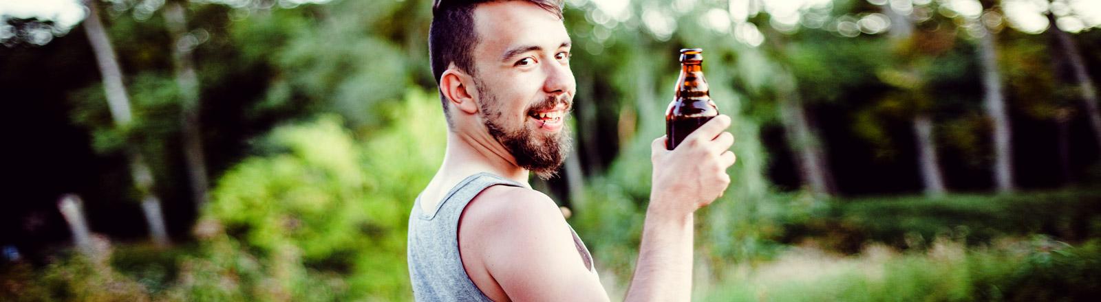 Ein Mann mit einer Flasche Bier in der Hand