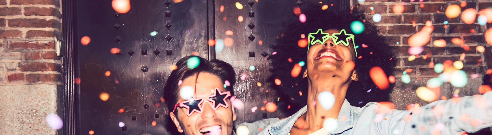 Zwei tanzende Menschen mit Konfetti