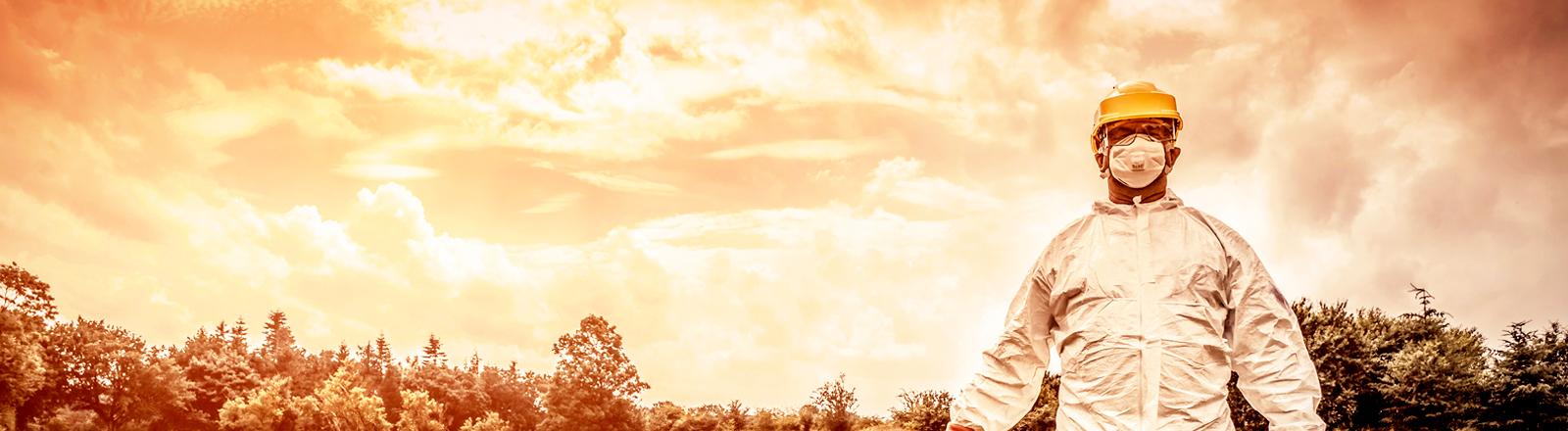 Mann in Schutzkleidung vor rotem Himmel