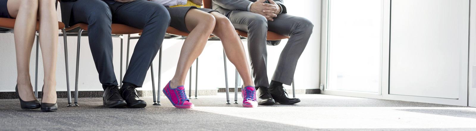 Männer und Frauen mit unterschiedlichen Schuhen auf Stühlen