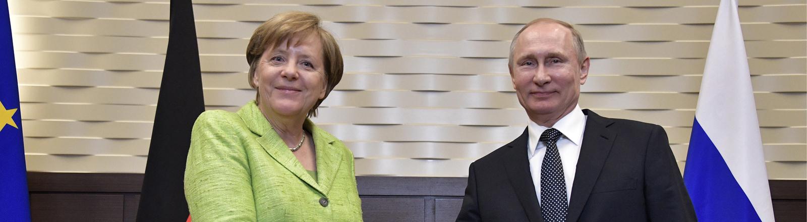Angela Merkel und Vladimir Putin schütteln sich die Hand