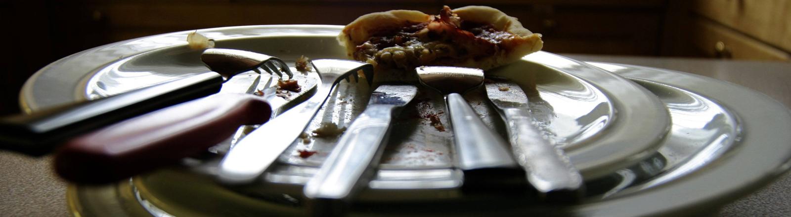 Gestapelte Teller, auf denen noch ein Rest Pizza liegt