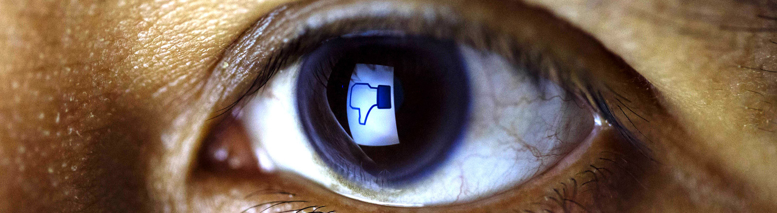Auge mit einem Facebook-Daumen-Runter in der Pupille