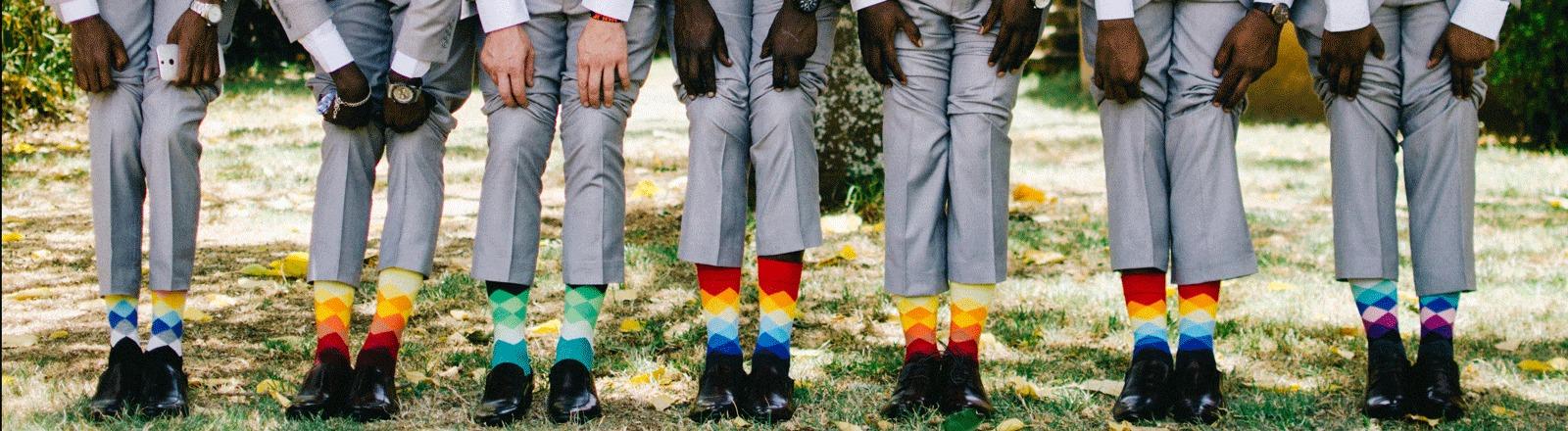 Männer im Anzug zeigen ihre bunten Socken
