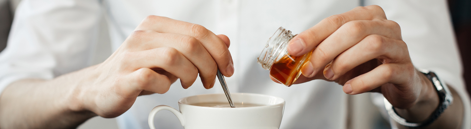 Mann schüttet sich Honig in den Tee