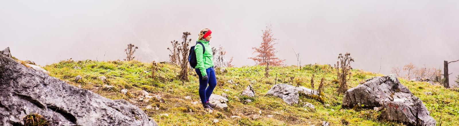 Frau mit Wanderklamotten auf einem kargen Hügel
